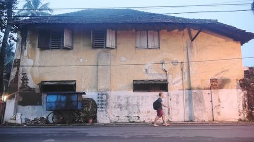 Two Caucasian Guys Passing By A Big Old House With Cracked Painted Walls In Kochi, India - Medium Sh