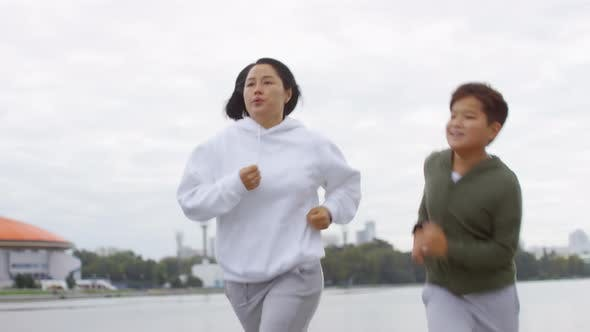 Thumbnail for Athletic Asian Mother and Son Jogging Outdoors along Urban Riverside