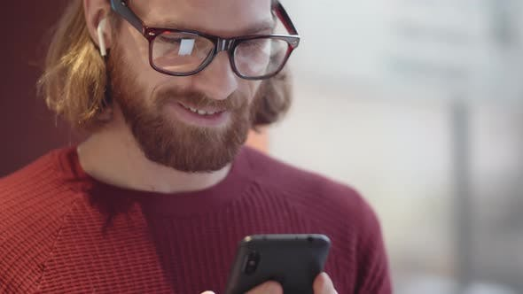 Thumbnail for Cheerful Caucasian Hipster Typing on Smartphone in Public Place