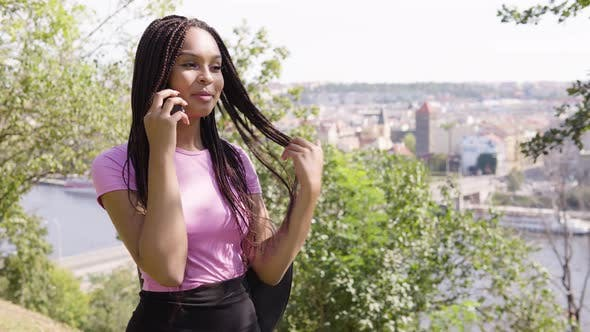 Thumbnail for A Young Black Woman Talks on a Smartphone with a Smile - Trees and a Cityscape in the Background