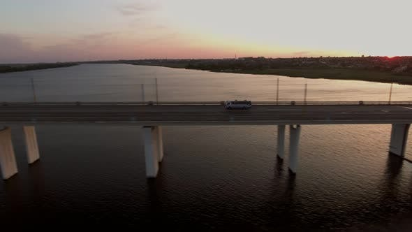 Thumbnail for Aerial Shot of a Long Bridge with a Moving Bus in Ukraine at Sunset in Summer