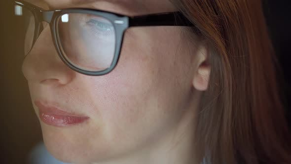 Thumbnail for Woman in Glasses Looking on the Monitor and Surfing Internet. The Monitor Screen Is Reflected in the
