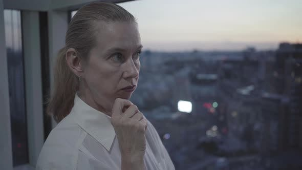 Thumbnail for Close-up Portrait of Thoughtful Confident Woman Standing on Glazed Balcony at Dusk. Mid-adult
