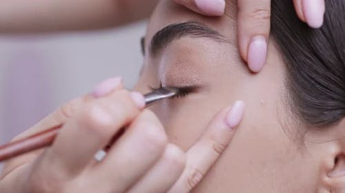 Make Up Artist Lining Eyes of Asian Girl with Brush and Eyeshadows, Close Up