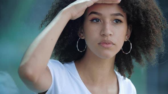 Thumbnail for American African Ethnic Girl schaut in Distanz mit Ihrer Hand zur Stirn, auf der Suche nach etwas