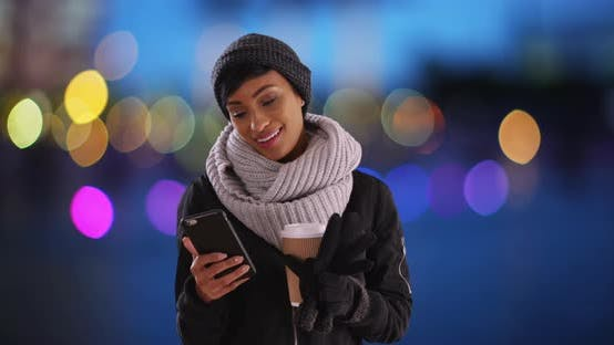 Thumbnail for Cute black woman in her 20s texting on phone in setting with blue bokeh lights