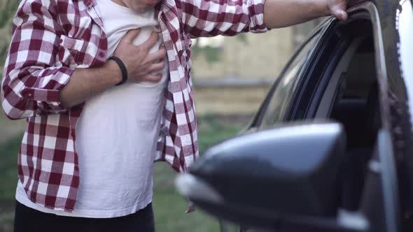 Unrecognizable Adult Caucasian Man Having Heart Attack Standing at Car Outdoors