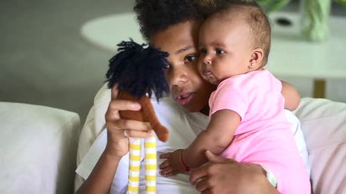 Older Biracial Brother Hold Infant Sister and Use Doll to Play with Her