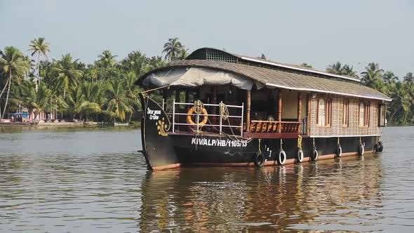 River side view of a houseboat passing by, with palm trees in the background, Kerala Backwaters, Ind