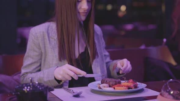 Cover Image for Beautiful Young Woman Eating Meat Grilled with Vegetable in the Modern Restaurant