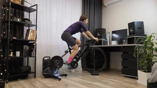 Woman is cycling on smart trainer at home. Indoor cycling