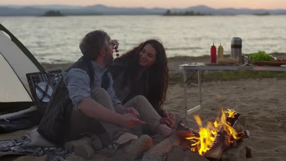 Thumbnail for Loving Couple Enjoying Picnic by Campfire on Beach