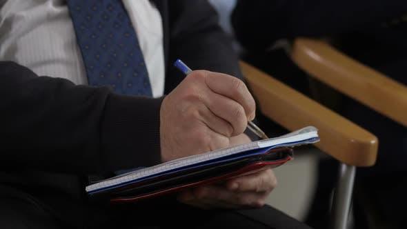 Cover Image for Closeup Man's Hands Writing Information at Seminar