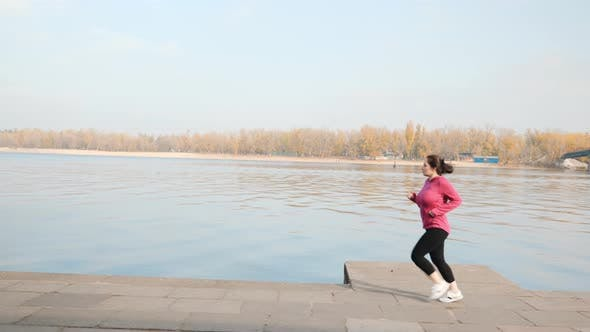 Chubby young woman running in city promenade as a part of weight loss program. Running concept