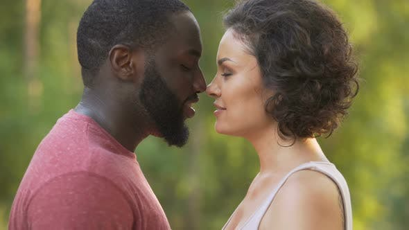 Thumbnail for Black male and white female delicately touch noses and smile happily afterwards