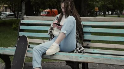 Young skater girl texting outdoors.