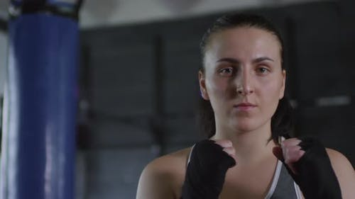 Young Female Boxer Holding Hands in Defensive Position and Posing for Camera