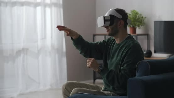 Man Is Sitting at Home and Using Virtual Reality Goggles Gesticulating By Hands Swiping and Zooming