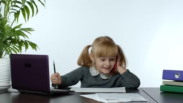 Lustige kleine Kind-Boss-Managerin, die emotional auf dem Handy spricht, am Computertisch sitzt