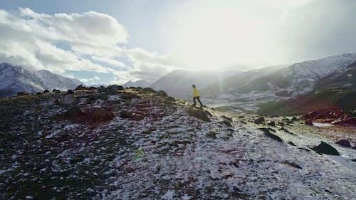 Mann stehend auf Rock Peak Snowy Winter Mountain Range Achievement Erfolg Ausgestreckte Arme Happines
