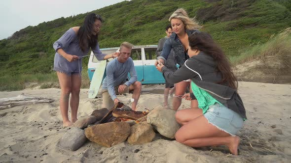 Thumbnail for Group of friends at beach hanging out by campfire roasting marshmallows