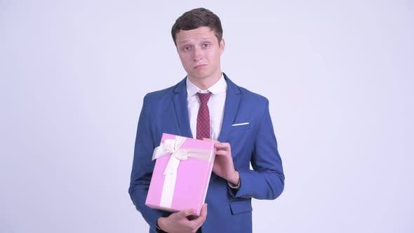 Cover Image for Happy Young Handsome Businessman Opening Gift Box