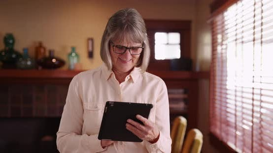 Thumbnail for Happy older woman playing with portable tablet computer in her living room