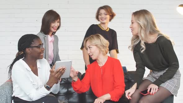 Thumbnail for Group of Female Blogger Professionals Working at Tablet Sitting at Table