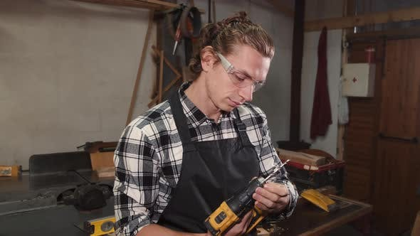 Craftsman with Electric Drill in Hands Standing in Workshop