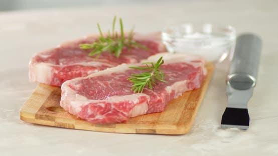 Raw Steak Beef Striploin on a Cutting Board Rotates.
