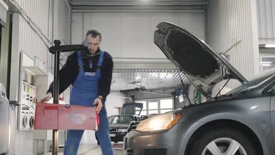 Autoservice. Mechaniker stellt Scheinwerfer ein. Abblendlicht, Fernlicht. Breiter Schuss