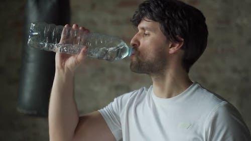 Mann trinkt Wasser aus der Flasche im Fitnessstudio
