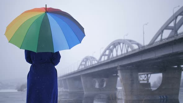 Thumbnail for Female in Coat with Rainbow Umbrella During Snow
