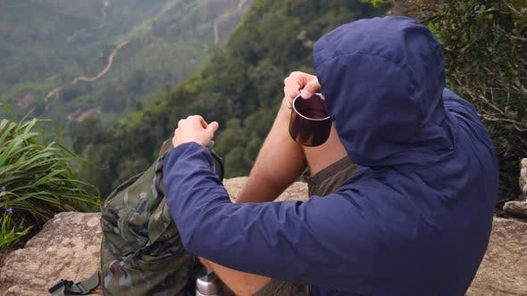 Thumbnail for Young Man Drinking Tea In Mountains. Hiking Camping Lifestyle Concept