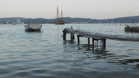Cover Image for A Boat Tied To a Wooden Pier in the Sea in the Evening