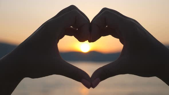 Thumbnail for Woman Making Heart Her Through Hands with Golden Sundown at Background. Silhouette of Female Arms