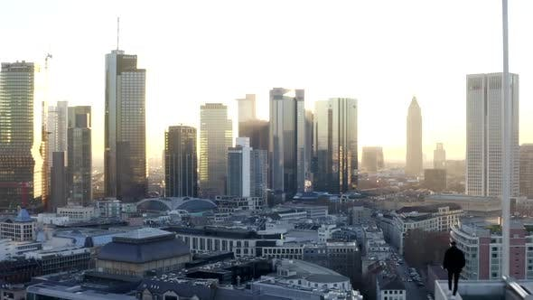 Thumbnail for AERIAL: Confident Young Man, Guy Walking on Rooftop in Skyline of Frankfurt Am Main, Germany with