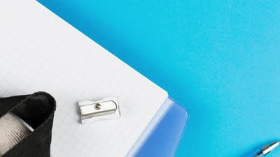 School Supplies Lie on a Pastel Blue Background Together with