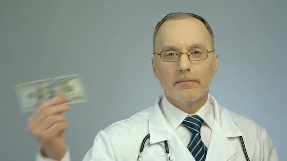 Cover Image for Male Therapist Showing One Hundred Dollars Bill, Paid Health Care Services