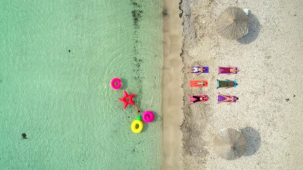 Thumbnail for Aerial view of people lying in yoga pose on on the with inflatables.