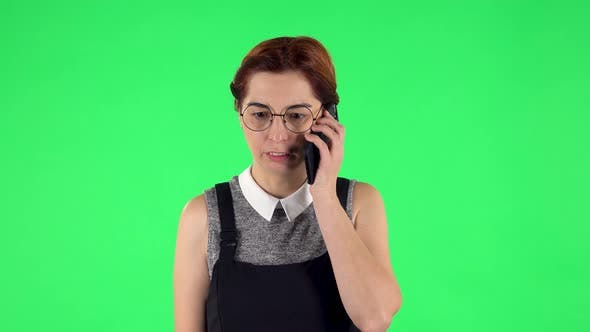 Thumbnail for Portrait of Funny Girl in Round Glasses Is Angrily Talking for Mobile Phone. Green Screen