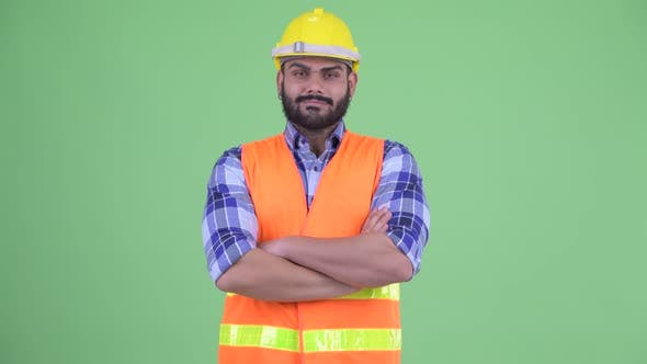 Thumbnail for Happy Young Overweight Bearded Indian Man Construction Worker Smiling with Arms Crossed