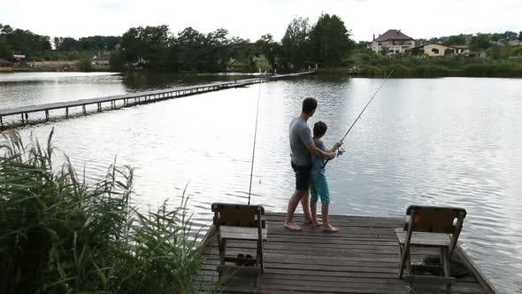 Thumbnail for Father and Son Angling at Tranquil Lake in Summer