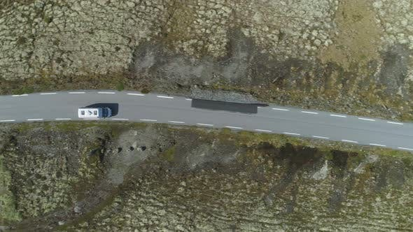 Cover Image for White Motorhome Car Is Going on Mountain Road in Norway. Aerial Vertical Top-Down View