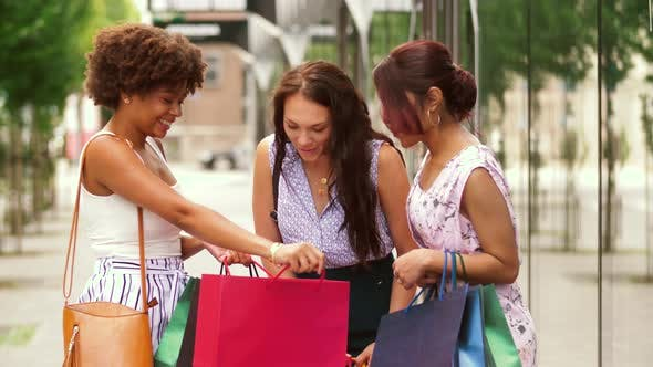 Thumbnail for Happy Women Showing Shopping Bags in City