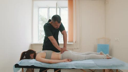 Osteopath Treatment - the Doctor Pushing on the Butt of Young Woman