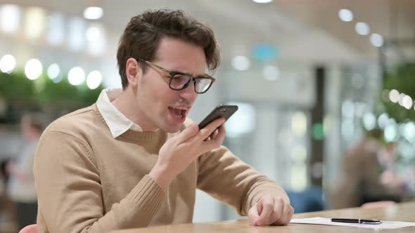 Angry Male Designer Talking on Smartphone in Office