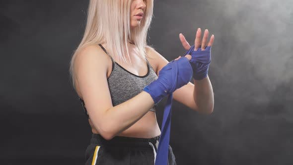 Female Athlete Dressed in Tank Top Wrapping His Fists By Blue Elastic Bandages