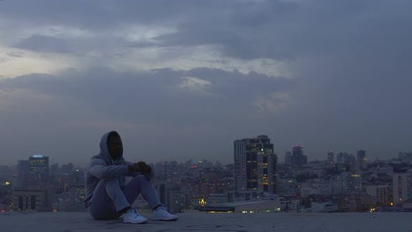 Thumbnail for Latin man meditating on roof of skyscraper trying to make important decision