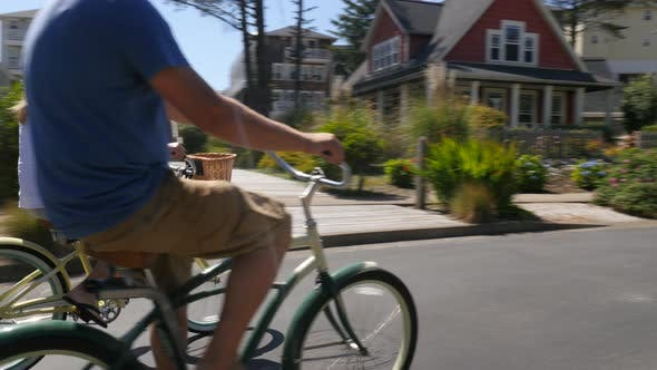 Thumbnail for Couple riding bicycles together in coastal vacation community